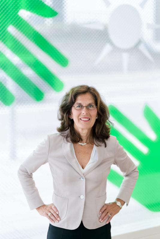 Managerportrait: Dr. Angela Kalous,  Abteilungsleiterin Forschung der Baden-Württemberg Stiftung in Stuttgart im Konferenzraum der Stiftung. Im Hintergrund sieht man große, grüne Hände und eine Sonne, die als Symbol nach außen großflächig auf die Außenscheiben des Raumes geklebt sind.