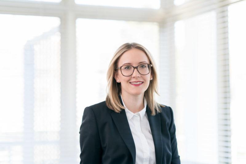 Managerportrait: Eine Kollegin einer Anwaltskanzlei in einem hell erleuchteten Konferenzraum. Sie trägt eine große Brille und trotz der Ausleuchtung mit einer Blitzanlage gibt es keine Spiegelungen im Brillenglas.