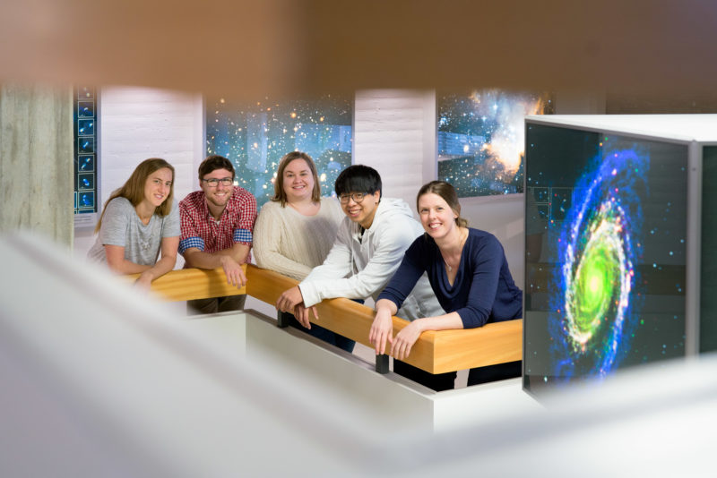 Group shot:  Group portrait of a working group in astronomy research. All stand in the stairwell and are surrounded by photos of star galaxies.