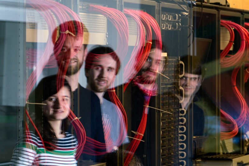 Group shot: Portrait of a working group at a computing institute of a university. The employees are reflected in the glass pane to the server room, where thick red cables lead into the computer cabinets.