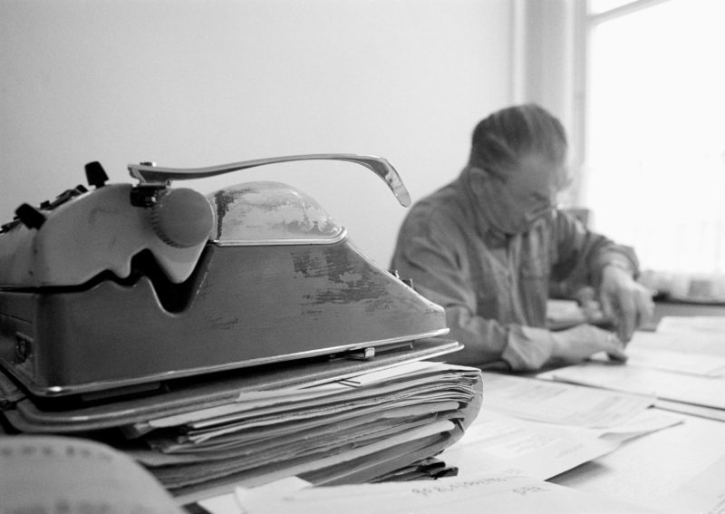 Black and white reportage photography at various workplaces in the early nineties: Office of a civil servant. In the foreground is a worn out typewriter on a stack of files.