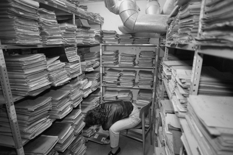 Black and white reportage photography at various workplaces in the early nineties: An employee is searching for files in the basement archive of a tax office.