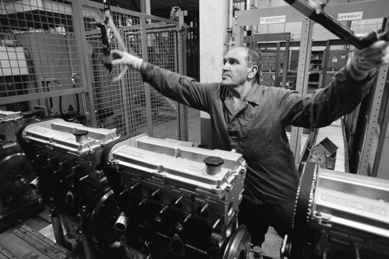 Black and white reportage photography at various workplaces in the early nineties: A so-called guest worker on the production line of a four-cylinder gasoline engine for passenger cars. He reaches for a tool hanging from the ceiling.