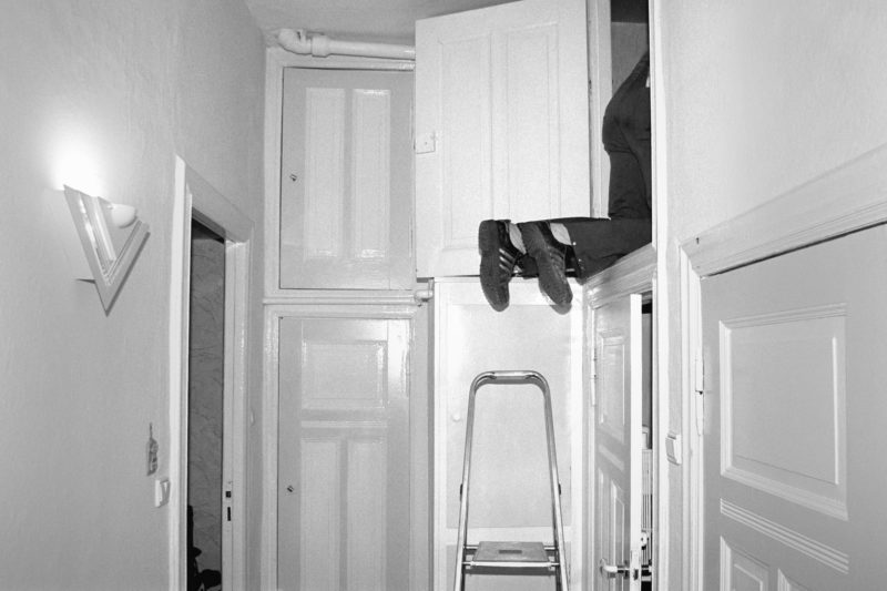 Black and white reportage photography at various workplaces in the early nineties: A plumber climbs into the wall cupboard of a typical old Berlin backyard apartment to repair a sewage pipe.