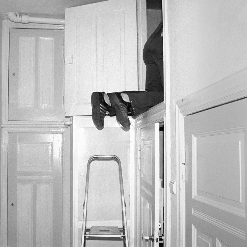 Luftaufnahmen und Drohnenfotografie: Schwarz-Weiss-Reportagefotografie an verschiedenen Arbeitsplätzen Anfang der neunziger Jahre: Ein Klempner klettert in den Wandschrank einer typischen alten Berliner Hinterhauswohnung um ein Abwasserrohr zu reparieren.