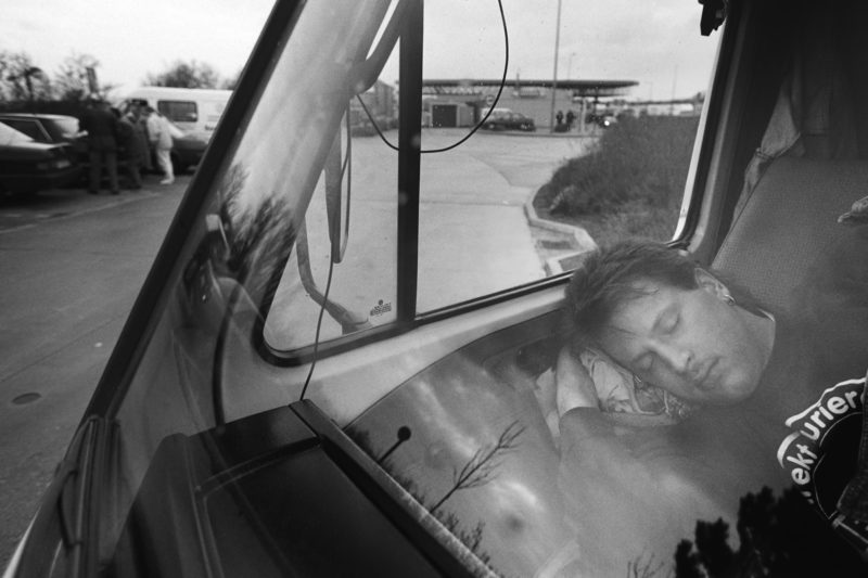 Black and white reportage photography at various workplaces in the early nineties: At a rest area, a courier driver lies asleep in the passenger seat of his van.