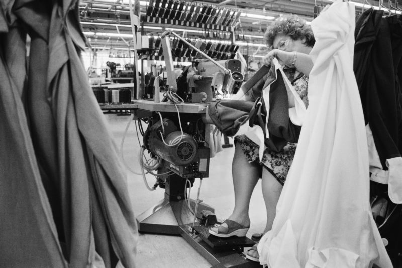 Black and white reportage photography at various workplaces in the early nineties: A seamstress at one of the last German textile factories is handling the fabrics of a pair of men