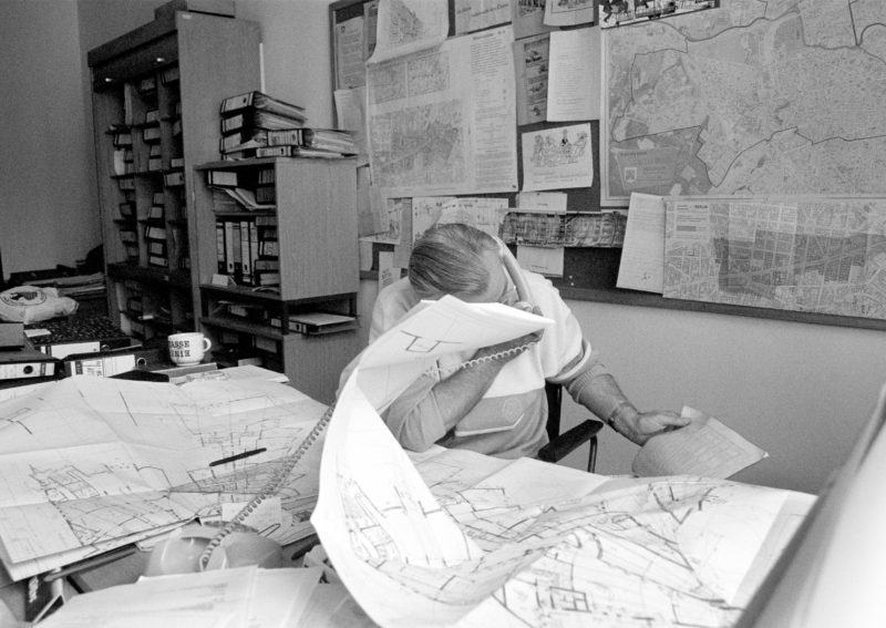 Black and white reportage photography at various workplaces in the early nineties: Office of a city planner. With the handset in his hand he scrolls through the telephone directory while his desk and the wall is covered with building plans.