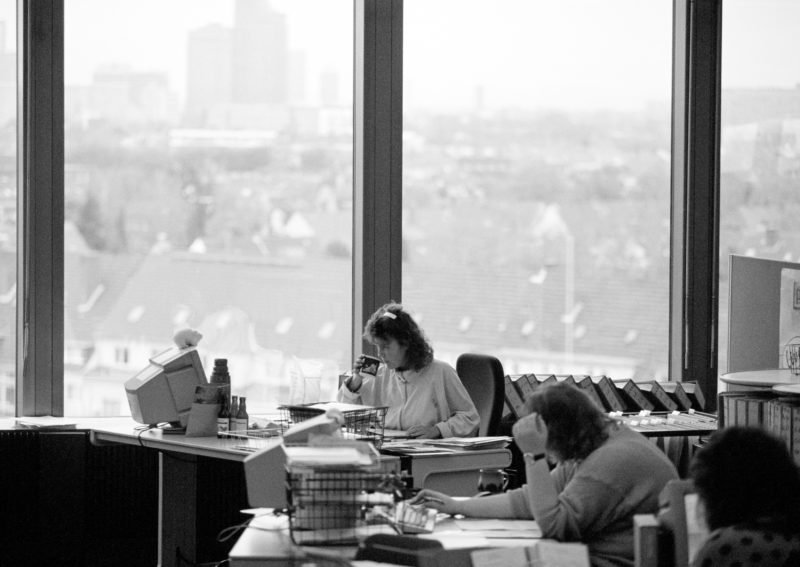 Black and white reportage photography at various workplaces in the early nineties: Women work in the modern, fully glazed open-plan office of an insurance company. There are paper files everywhere.