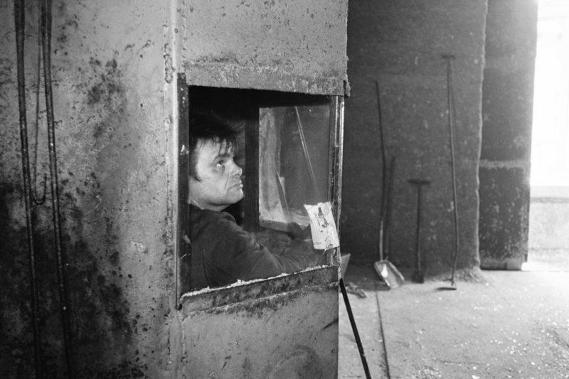 Schwarz-Weiss-Reportagefotografie an verschiedenen Arbeitsplätzen Anfang der neunziger Jahre: In einer Verzinkerei in Ostdeutschland schaut ein Arbeiter aus einer Schutzkabine.