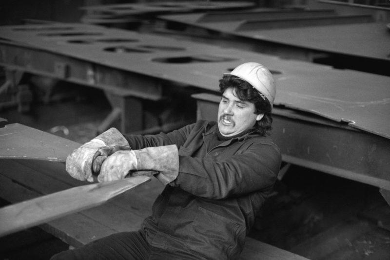 Schwarz-Weiss-Reportagefotografie an verschiedenen Arbeitsplätzen Anfang der neunziger Jahre: Ein Werftarbeiter in Rostock zieht per Hand ein am Kran hängendes schweres Stahlstück in die richtige Position, an der es verschweisst werden soll.
