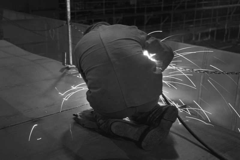 Black and white reportage photography at various workplaces in the early nineties: A worker at a shipyard is welding on the deck of a pontoon on which refugee accommodation is to be built.