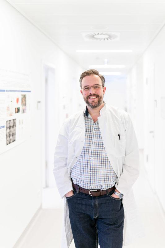 Portrait eines Augenarztes im Flur des Forschungsinstituts an einer Universitätsklinik.