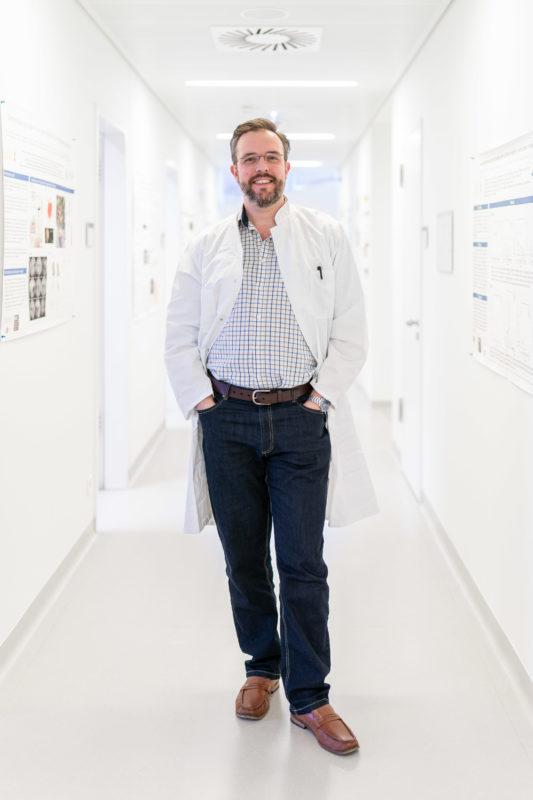 Portrait eines Augenarztes. Er steht im Flur im Forschungsbereich seiner Universitätsklinik.