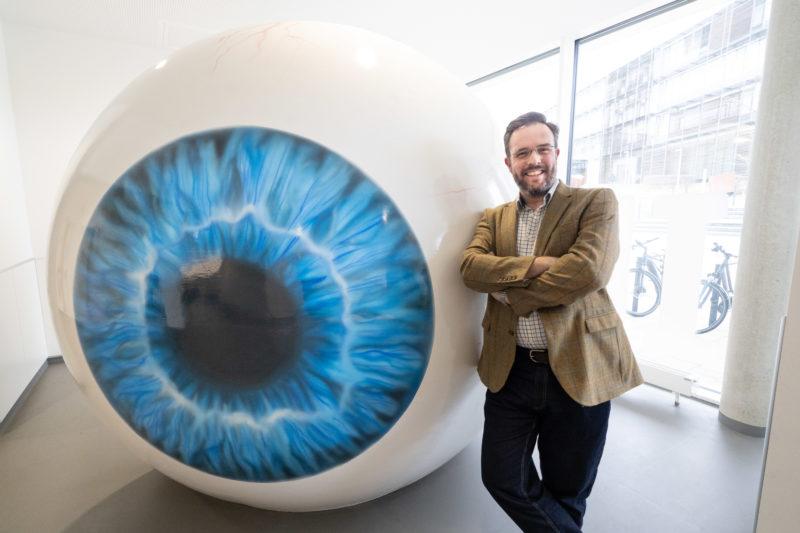 Portrait eines Augenarztes an einer Uniklinik. Zum Glück für mich als Fotograf konnte ich dank dm großen Auge im Foyer der Klinik einen einfachen optischen Bezug zum Thema herstellen.