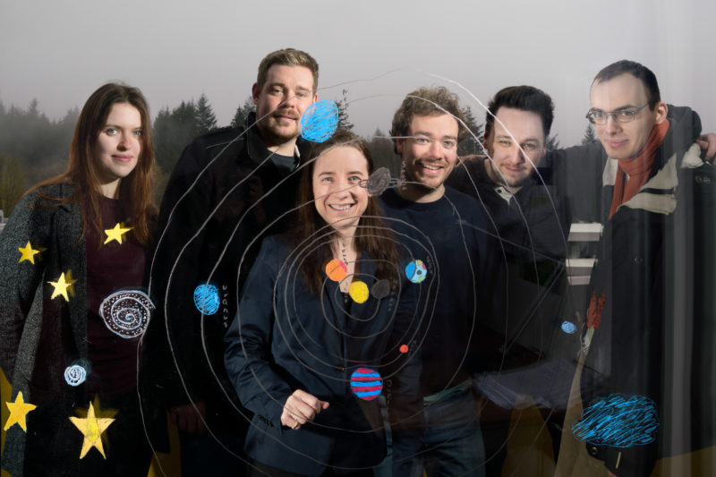 Group shot: Six colleagues from an astronomy research group stand behind a glass pane on which the child of an employee has painted the Earth