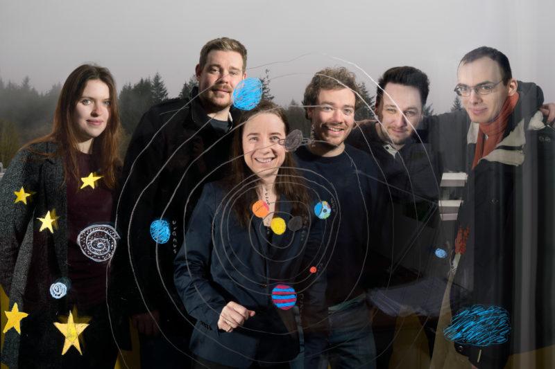 Gruppenfoto: Sechs Kolleginnen und Kollegen einer Astronomie-Forschungsgruppe stehen hinter einer Glasscheibe, auf der das Kind einer Mitarbeiterin das Sonnensystem der Erde gemalt hat.