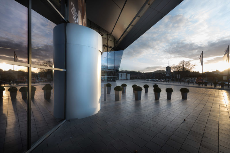 Architectural photography: Exterior view of an entrance area of a company at sunset. Plant tubs line the access path over the pavement of the forecourt.