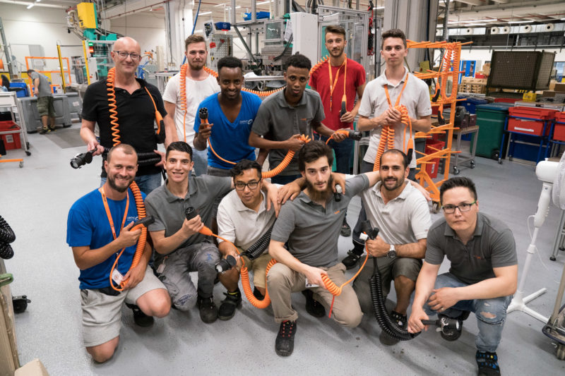Group photo: Trainers and trainees at a cable manufacturer. The trainees come from many countries, there are some refugees with them. All of them have charging cables for electric vehicles in their hands or have them hanging around their neck.