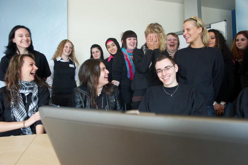 Reportagefotografie: In der kaufmännischen Ausbildung dominieren weibliche Auszubildende. In einer Gruppe sitzt der einzige Mann in der Mitte und alle freuen sich.