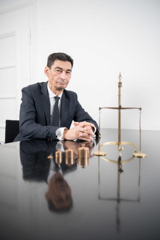Managerportrait: Ein Bankmanager sitzt mit gefalteten Händen an einem spiegelnden schwarzen Tisch.Vor ihm steht eine goldene mechanische Waage mit nebeneinander aufgereihten Gewichten. Das Foto ist mit Blitzanlage ausgeleuchtet und wird für die Öffentlichkeitsarbeit verwendet.