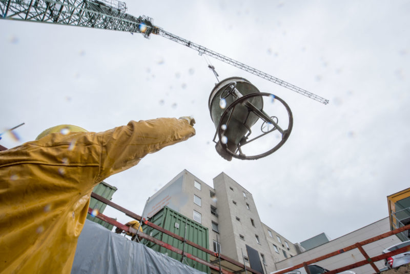 Editorial photography: In the rain a full concrete bucket floats on the crane to the construction site. A worker reaches for it to empty it at the right place.