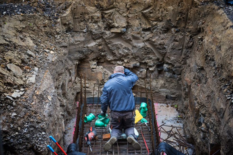 Editorial photography: A worker kneels in a pit to lay drainage pipes. You can see him from behind.