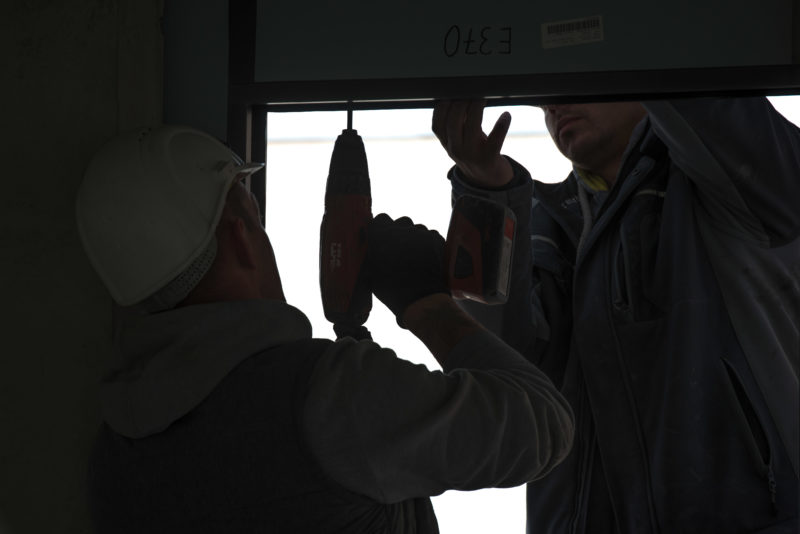 Editorial photography: Two window manufacturers assemble a frame. All you see are their silhouettes and the one  of the drill.