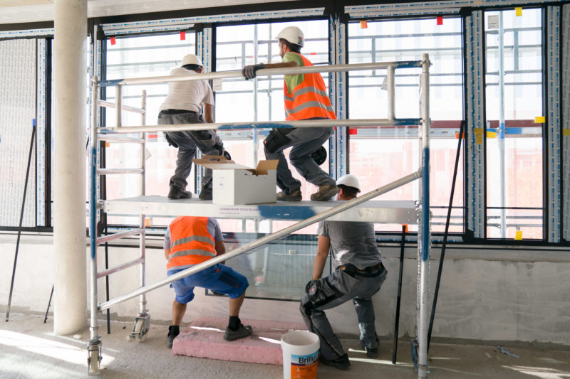 Editorial photography: Four window manufacturers lift a large glass pane into position in the shell of an office complex. Two stand on the floor and two on a scaffolding.