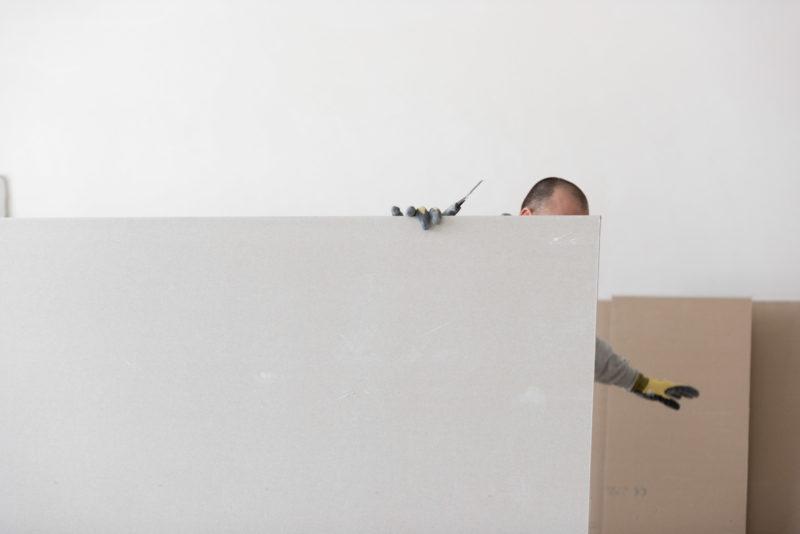 Reportagefotografie: Beim Innenausbau schneidet ein Arbeiter die Gipswände mit einem Messer. Er verschwindet hinter der Gipsplatte, man sieht seine Handschuhe und das Messer.