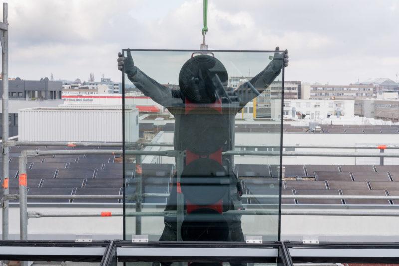 Reportagefotografie: Ein Fassadenbauer balanciert eine riesige Glasscheibe an ihre Position, die ihm am Kran hängend angeliefert wird.
