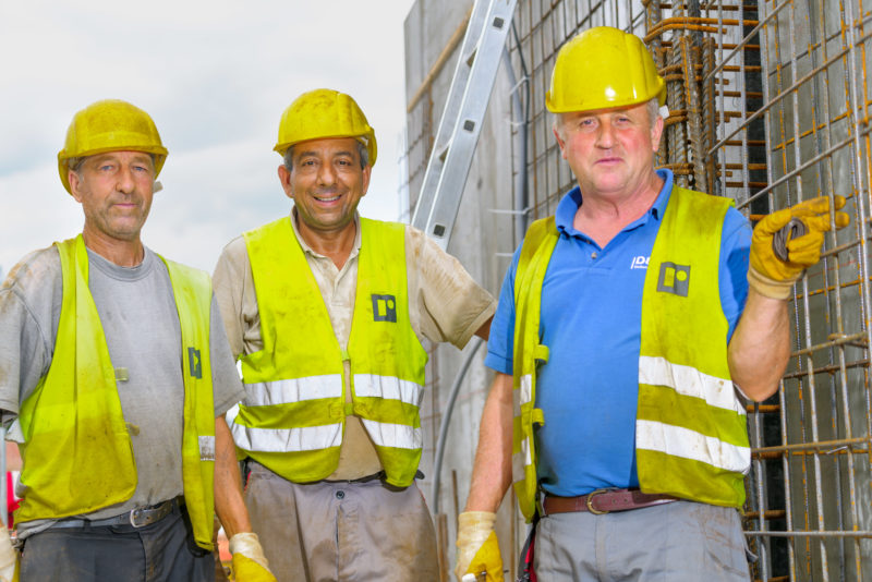 Editorial photography: Three construction workers in signal vests and yellow safety helmets proudly look into the camera. In the background you can see the reinforcing irons for a wall.