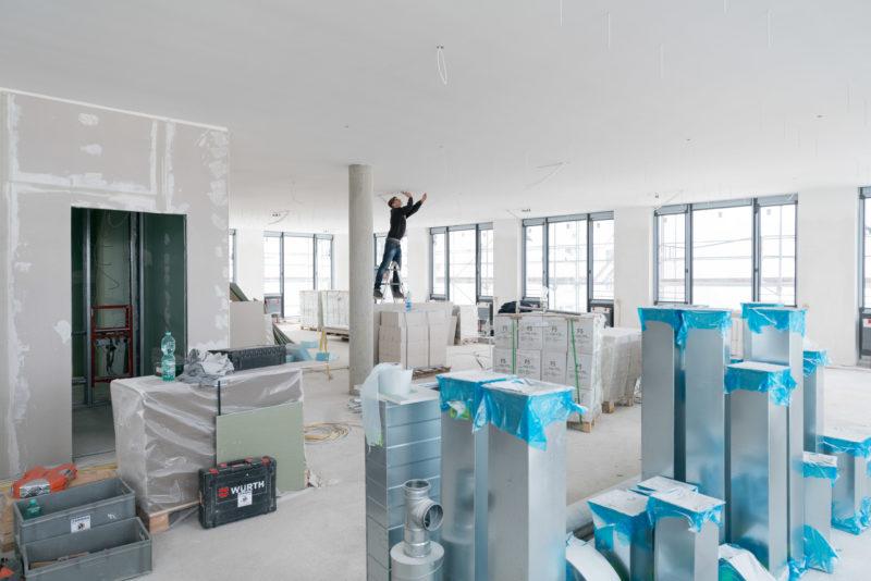 Reportagefotografie: Auf einer Etage stehen jede Menge Materialien, die noch verbaut werden müssen. Ein Monteur steht dazwischen auf einer Leiter und arbeitet an der Decke.