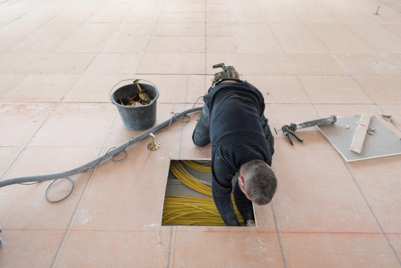 Reportagefotografie: Ein Elektriker greift durch eine aufgesägte Öffnung in den Kabelzwischenboden.