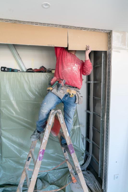 Reportagefotografie: Ein Arbeiter verschwindet mit seinem Kopf hinter der Verkleidung eines Kabelschachtes. Er steht auf einer Bockleiter und hat einen Werkzeuggürtel umgebunden.