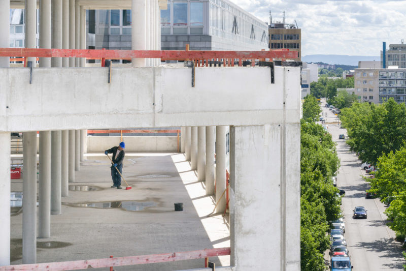 Editorial photography: A worker with a blue helmet sweeps the concrete floor in the still windowless building. You can see the surrounding area with a road with cars and green trees.