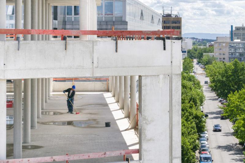 Reportagefotografie: Ein Arbeiter mit blauem Helm kehrt den Betonboden im noch fensterlosen Gebäude. Man sieht die Umgebung mit einer Straße mit Autos und grünen Bäumen.