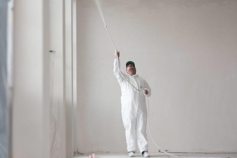Editorial photography: A painter in white overalls sprays white paint on the ceiling in a white environment.