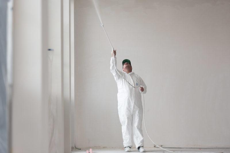 Reportagefotografie: Ein Maler in weissem Overall sprüht in weisser Umgebung weisse Farbe an die Decke.