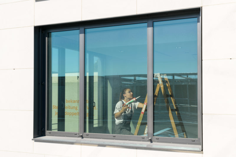 Editorial photography: A painter climbs the ladder to draw joints on the ceiling of an office. She is photographed from outside through a large window in which the blue sky is reflected.