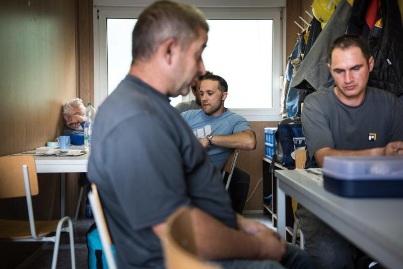 Reportagefotografie: Arbeiter sitzen in der ersten Pause am Morgen in einem Containerraum.