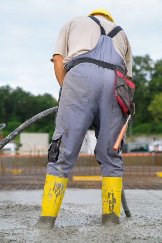 Editorial photography: A worker photographed from behind stands with yellow rubber boots in the still liquid concrete of a suspended ceiling, to compact it with a vibrating surface.