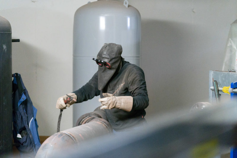 Editorial photography: A steel constructor is welding on a large pipe of the heating system in the shell in the basement of a building. He wears welding goggles, a leather hood and protective gloves.