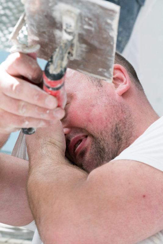 Reportagefotografie: Ein Stuckateur wischt sich den Schweiss aus dem Gesicht. Er hat eine Kelle der Hand.