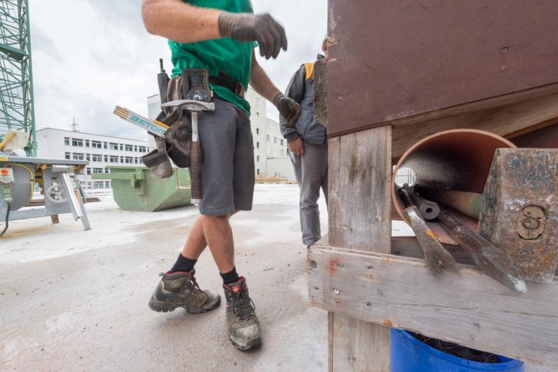 Reportagefotografie: Bauarbeiter mit Werkzeuggürtel. Darin befinden sich Hammer, Funkgerät und Massstab.