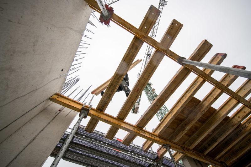 Reportagefotografie: Ein Arbeiter balanciert mit einem großen Balken auf der offenen Verschalung für eine Zwischendecke. Von unten fotografiert. Über allem ragt der Kran.