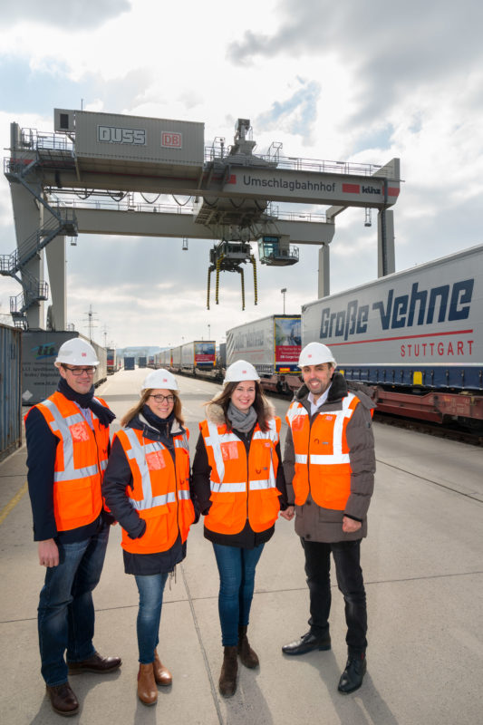 Group photo: Group picture of 4 visitors of a container station. In the background you can see a loading crane and freight car of the railway. All wear orange signal vests and white helmets.
