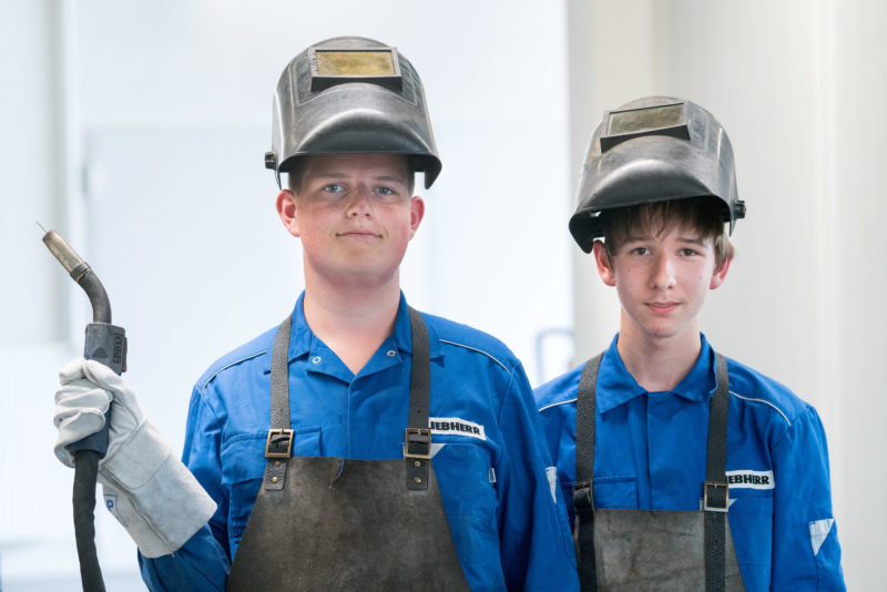Editorial photography: Two pupils during a practical training at Liebherr-Hydraulikbagger GmbH. They practice welding for the first time. For that, they wear helmets with a sweat visor, thick aprons and leather gloves.