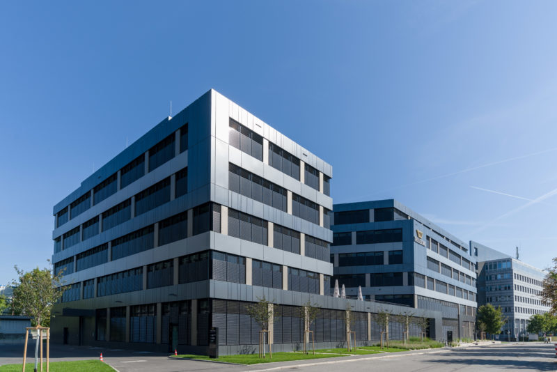 Architectural photography: General view of a new office building with a dark metal facade shining in the sun. The blue sky provides a good contrast between the architectural elements.