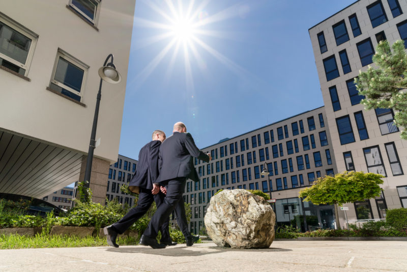 Architectural photography: Two employees leave their building in a modern office environment. You can see the sun against the blue sky between the towering companies in the area. In the foreground a round rock as decoration and behind it green trees and bushes.